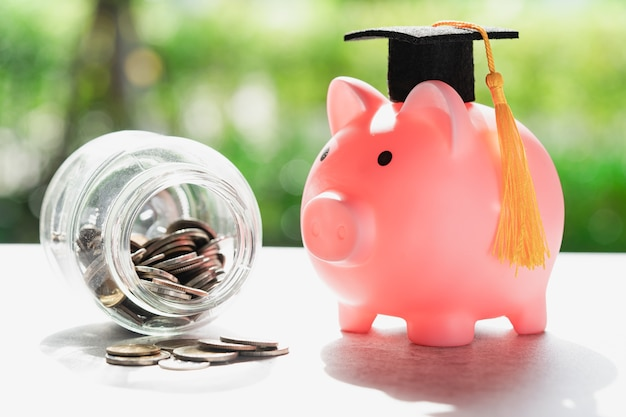 Save money coins in grass jar with piggy bank and graduation cap business finance education