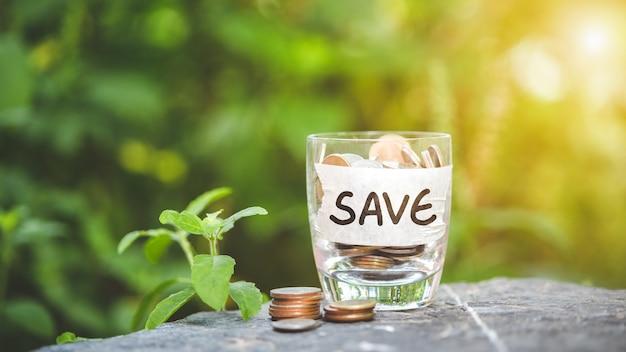 お金を節約するという概念。ガラスに集められたコインと積み重ねられたコインが置かれました。