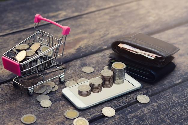 Save money concept with coin stack growing on smartphone, cart and wallet