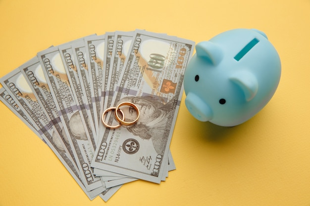 新婚旅行の結婚式の旅行のためにお金を節約するお金の紙幣に指輪を付けた貯金箱o
