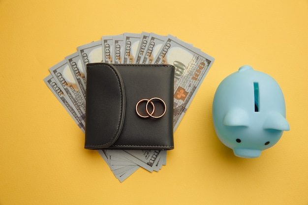 Save money for honeymoon, wedding trip. piggy bank with rings on wallet with money