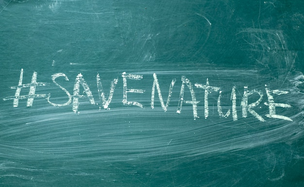 Save the nature hashtag it handwritten with white chalk on a green blackboard