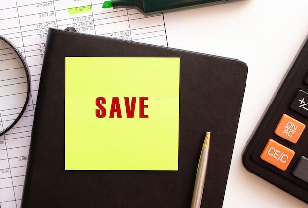Сохраните текст на наклейке на рабочем столе. дневник, калькулятор и ручка. финансовая концепция.