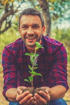 환경을 구하라! 행복한 청년이 땅에 식물을 뻗고 정원에 서 있는 동안 카메라를 보고 있다