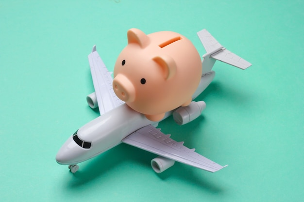 Save up for air travel. piggy bank with toy airplane on blue.