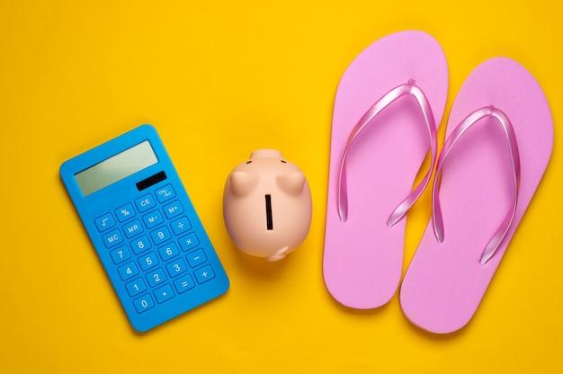 ビーチでの休暇のために貯金してください。電卓とビーチサンダル、黄色の貯金箱
