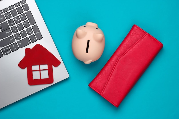Save up for housing. laptop, piggy bank with house figure, wallet on blue