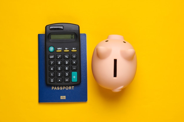 Save up for travel or emigration. piggy bank with passport, calculator on yellow