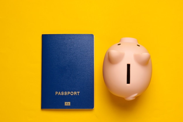 Save up for travel or emigration. piggy bank with passport on yellow