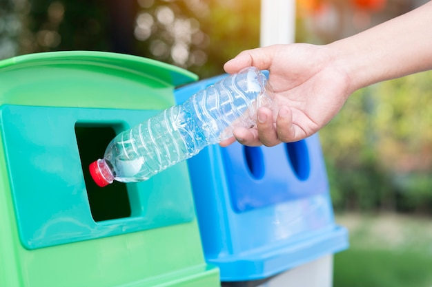 Save the world concept, hand throw plastic bottle into recycle bin