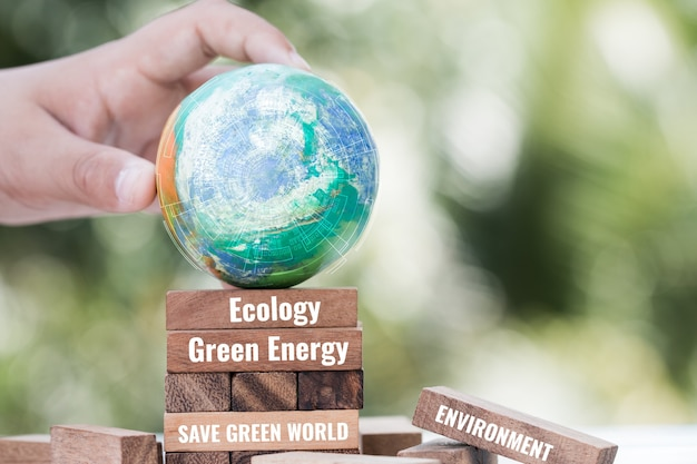 Save world or earth day concept. hands holding model globe clay with radar on wooden block tower for letter e.g green energy,save green world, environment. idea for natural environmental saving
