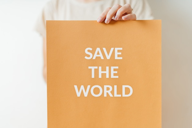 Save the world - ecology sign of protest for green future of planet. woman holding paper