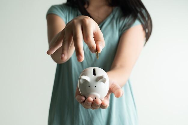 Сбережения и бизнес-концепция, милая девушка с копилкой и монетами дома