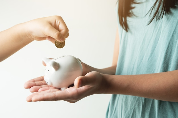 Экономия и бизнес-концепция, две маленькие девочки с копилкой и монетами дома