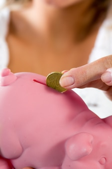Saving, blonde young woman with a piggy bank