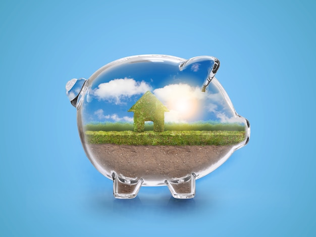 Saving to buy a house or home savings concept with grass growing in shape of house inside transparent piggy bank.