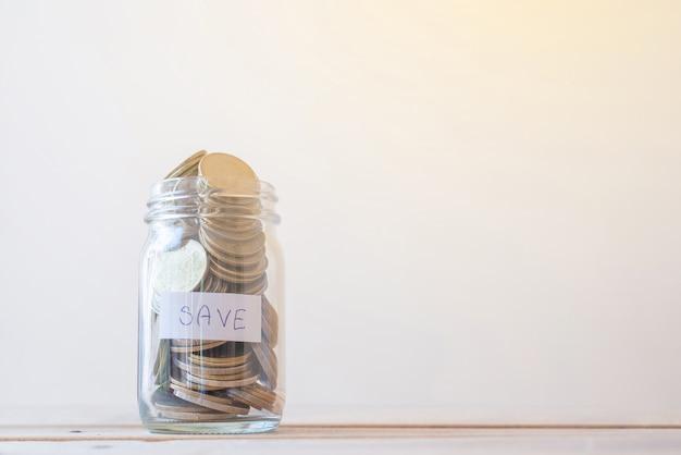 Сохранение монет в стекле на деревянном столе - концепция инвестиций, бизнеса, финансов и банковского дела