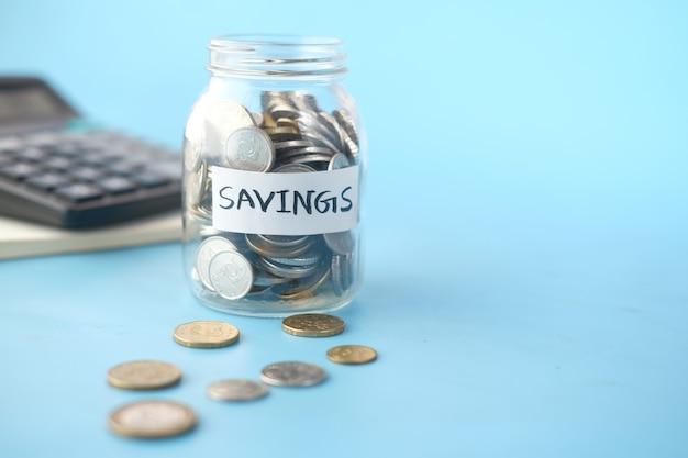 Saving coins jar and calculator on table