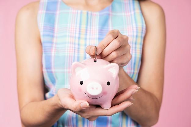 Saving concept. closeup of hand putting a coin into a pink piggybank.