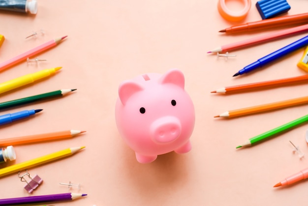 Saving for education or back to school concept, piggy bank and colorful marker, pencil and pen