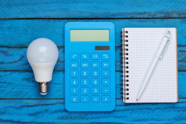 전기 절약. led 전구 및 계산기, 푸른 나무 표면에 노트북. 평면도