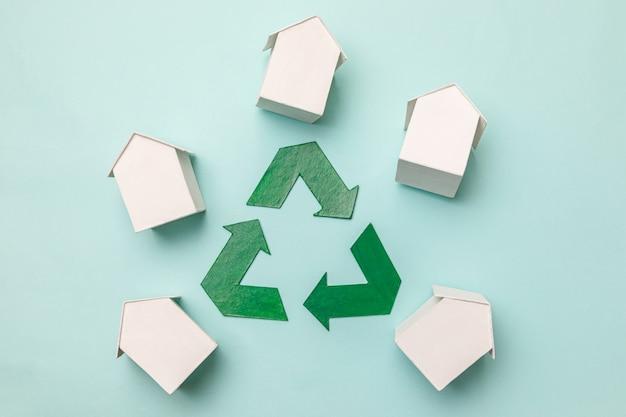 에너지 절약 친환경 지구 온난화 개념. 파스텔 블루 배경에 분리된 소형 흰색 장난감 모델 하우스와 재활용 기호로 간단하게 디자인합니다. 평평한 평면도 복사 공간.