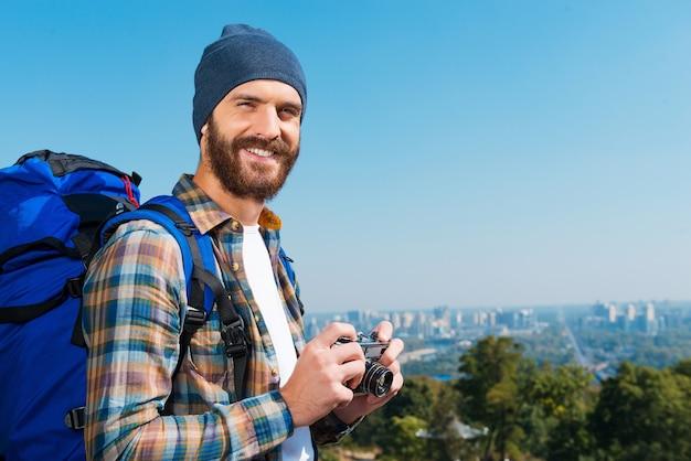 Сохранение каждого просмотра в памяти. красивый молодой человек несет рюкзак и смотрит в камеру через плечи с улыбкой, стоя на природе и держа камеру