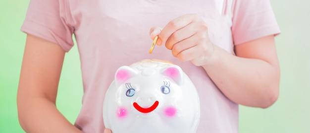 Saving, girl putting coin in piggy bank