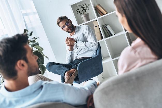 結婚を救う。セラピーセッションに座っている間心理学者に耳を傾ける若い夫婦