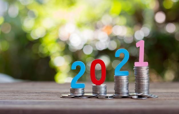 木の床のガラス瓶にお金とコインを節約します。将来のための投資コンセプト。ボケ味の背景