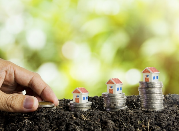 Saving money to build a house concept, house and coins in soil