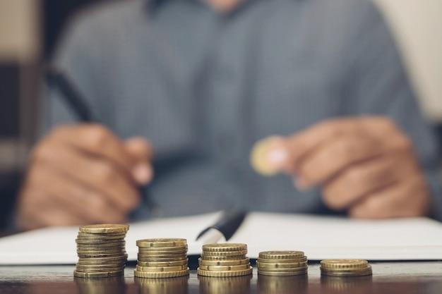 お金を節約。ビジネスマンの手は、貯蓄マネーファイナンスビジネスと裕福な成長の概念を示すためにスタックコインを置きます。 blackamoorの人々。