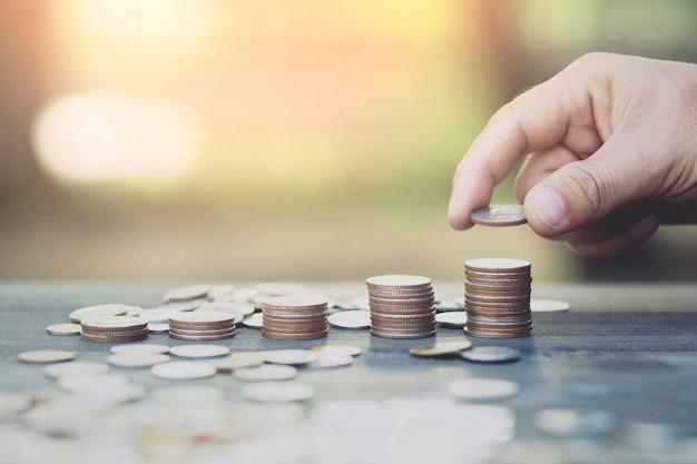 お金を節約。ビジネスマンの手は、スタック コインを置き、成長する貯蓄マネー ファイナンス ビジネスと裕福な概念を示します。
