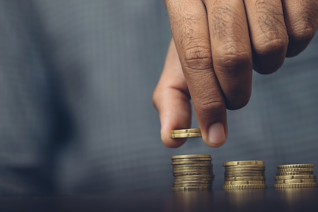 お金を節約。成長する貯蓄マネーファイナンスビジネスと裕福な概念を示すためにスタックコインを置くビジネスマンの手。
