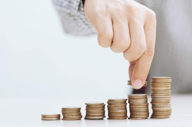 お金を節約。貯蓄の増加の概念を示すためにスタックコインを置くビジネスマンの手