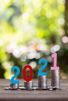 Saving money and coins in a glass bottle on a wooden floor. investment concept for the future. with bokeh background