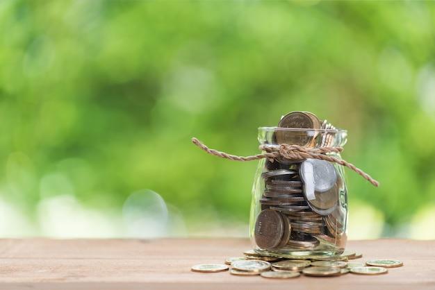 お金の概念、木製のテーブルの上のガラスの瓶にコインを保存