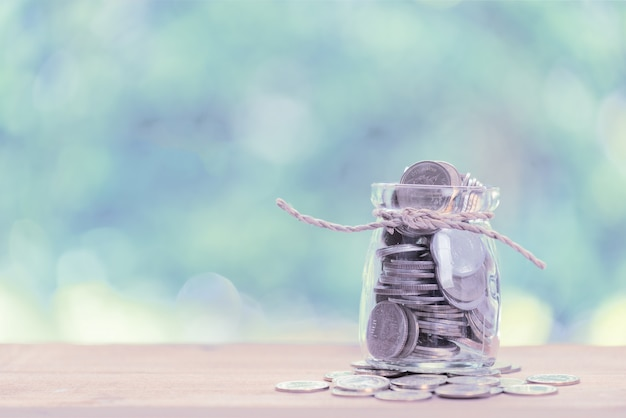 Saving money concept, money coins in glass jar on wooden table