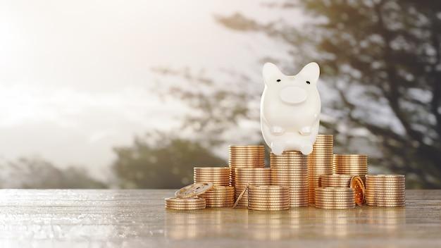 お金の節約の概念貯金箱のキャラクターをお金のコインスタックにコピースペースでプラスの収入成長