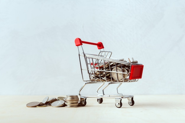 Saving money concept, shopping trolley or cart with coin