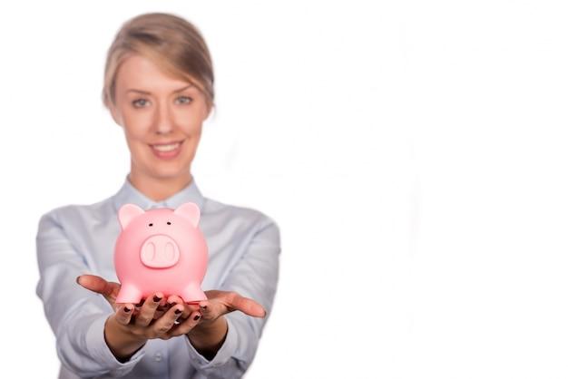 Экономия денег концепции - женщина улыбается счастливым и проведение piggy ба
