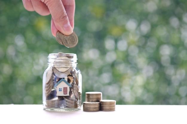 Экономия денег для подготовки в концепции будущего, модельный дом и золотые монеты в стеклянной бутылке на зеленом фоне, финансы и банковское дело