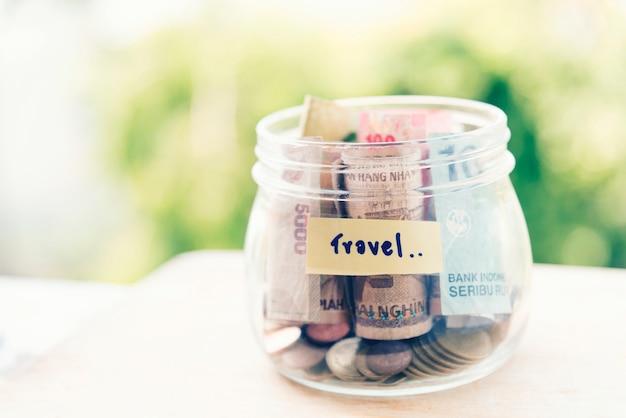 Экономия денег для концепции путешествия банку. копилка на пустом столе собирать банкноты и монеты