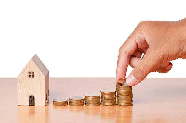 白い背景で隔離の木製の家のモデルとスタックにコインを置く手でお金を節約します。家の購入のための概念。クリッピングパス。