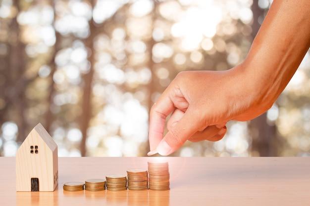 Экономия денег рука кладет монеты в стек с деревянной домашней моделью на размытом фоне листьев.