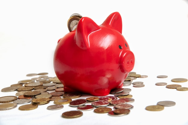 Экономя деньги. нужна открытая копилка с монетами, разбросанными монетами разных стран, на белом фоне, крупным планом.