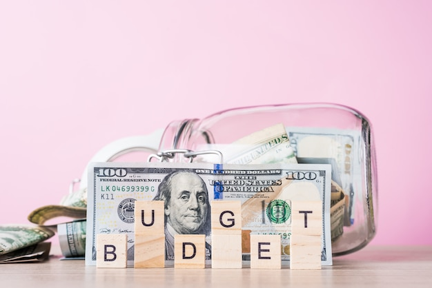 Saving money and planning budget . dollar bills in glass saving bank and word budget on a pink