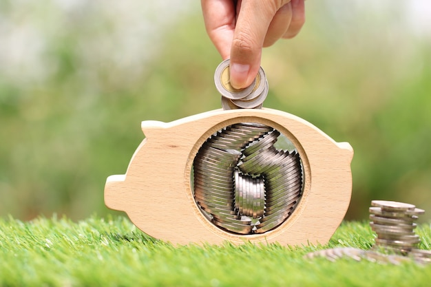 Saving money for prepare in future concept, woman hand putting a coin into piggy bank wood