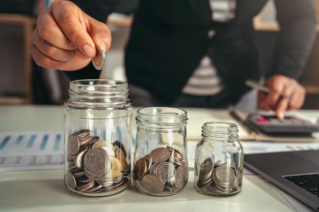 금융 용기 유리 개념에 동전을 넣어 손으로 돈을 절약