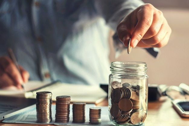 Saving money with hand putting coins in jug glass  financial